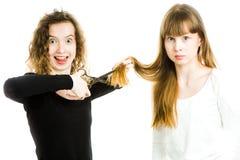 Två flickor med blonda hår och sax, ett som går att klippa hår arkivbild