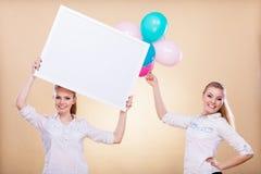Två flickor med det tomma brädet och ballonger Royaltyfria Bilder
