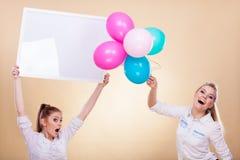Två flickor med det tomma brädet och ballonger Fotografering för Bildbyråer