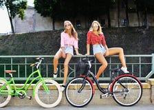 Två flickor med en utomhus- stående för cyklar Royaltyfria Foton