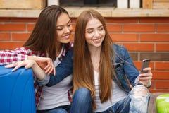 Två flickor med påsar som läser textmeddelandet, medan sitta på stationen royaltyfri foto
