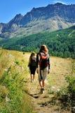 Två flickor med ryggsäckar i turismaktionen av de alpina bergen Royaltyfri Fotografi