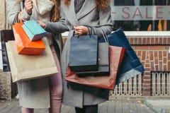 Två flickor med shoppingpåsar framme av show-fönstret med försäljningen som är skriftlig på den Royaltyfri Fotografi