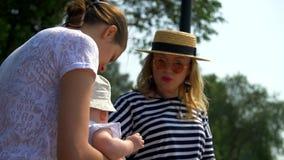 Två flickor meddelar med ett småbarn lager videofilmer