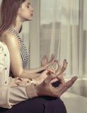 Två flickor mediterar i kontoret efter arbete arkivfoto