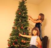 Två flickor near julgranen Arkivbild