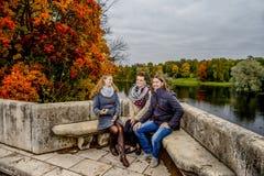 Två flickor och en grabb på en bänk fotografering för bildbyråer