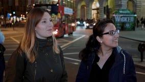 Två flickor på den Piccadilly cirkusen på natten - London sight vid natt arkivfilmer
