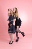 Två flickor på en rosa bakgrund royaltyfri foto