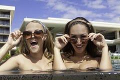 Två flickor på en simbassäng Arkivfoto