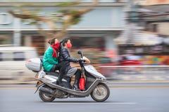 Två flickor på en sparkcykel med munlocket, Yiwu, Kina royaltyfria bilder