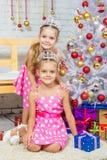 Två flickor på skönheten av julgranar royaltyfria foton