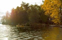 Två flickor paddlar en kanot i tidig höst arkivbild