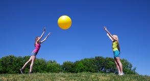 Två flickor play med den gula bollen Arkivbild