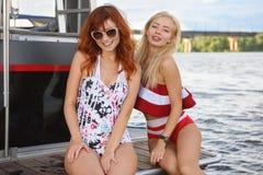 Två flickor poserar på yachten royaltyfri bild