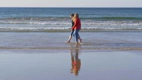Två flickor promenerar den sandiga stranden i nordligt - Irland på en kylig dag i höst stock video