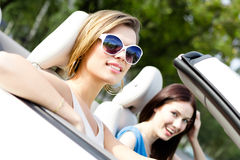 Två flickor rider cabrioleten royaltyfri bild