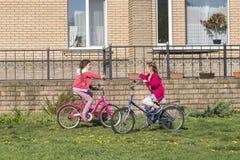 Två flickor rider en cykel Två systrar rider en cykel på gräsmattan framme av huset royaltyfri fotografi