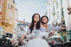 Två flickor rider på en motorcykel Den kinesiska flickan är i en framdel Brunettflickan sitter i mitt Det sista royaltyfria foton