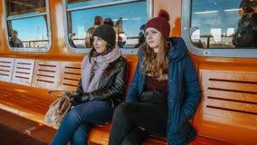 Två flickor rider Staten Island Ferry på en solig dag arkivbilder