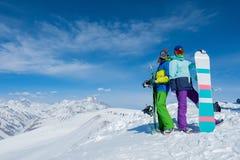 Två flickor rymmer snowboardbräden Vinter Bergen Royaltyfri Fotografi