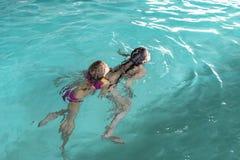 Två flickor simmar i pölen Två systrar i pölen Två lyckliga flickor spelar i pölen Härliga flickor simmar och ha gyckel i vatten arkivfoto