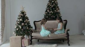 Två flickor sitter på golvet av huset med julgåvor och en girland Flickor som spelar med girlanden arkivfilmer
