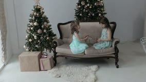Två flickor sitter på golvet av huset med julgåvor och en girland Flickor som spelar med girlanden stock video