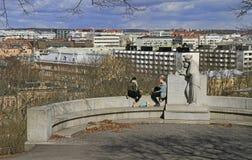 Två flickor sitter på statyn mot bakgrund av cityscape Royaltyfria Bilder