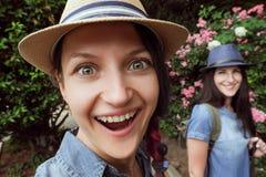 Två flickor skrattar och att posera i trädgården med blommande rosor på en fisheyelins Royaltyfria Bilder