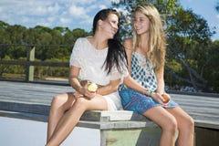 Två flickor som äter äpplen vid liten vik Arkivfoto