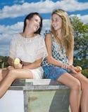Två flickor som äter äpplen vid liten vik Royaltyfria Foton