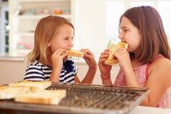 Två flickor som äter ost på rostat bröd i kök Arkivfoton