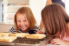Två flickor som äter ost på rostat bröd i kök Arkivbild