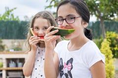 Två flickor som äter vattenmelonen Arkivfoto