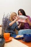 Två flickor som öppnar gåva Arkivbild