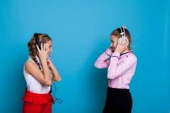Två flickor som bär hörlurar som lyssnar till musik och att dansa arkivfoton