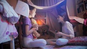 Två flickor som berättar läskiga berättelser i tipitält i sovrum på natten lager videofilmer