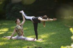 Två flickor som gör yoga, övar parkerar in Fotografering för Bildbyråer