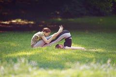 Två flickor som gör yoga, övar parkerar in Royaltyfria Bilder