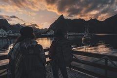 Två flickor som håller ögonen på soluppgången på en brygga i Reine i de Lofoten öarna, Norge arkivfoto