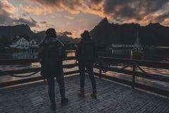 Två flickor som håller ögonen på soluppgången på en brygga i Reine i de Lofoten öarna, Norge fotografering för bildbyråer