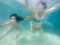 Två flickor som har att simma för gyckel som är undervattens- fotografering för bildbyråer