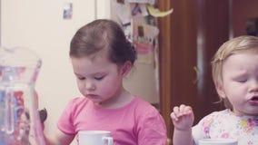 Två flickor som har frukosten på tabellen stock video