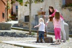Två flickor som har gyckel med dricksvattenspringbrunnen royaltyfri foto