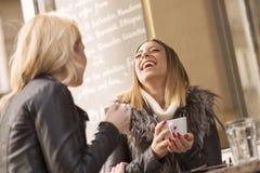 Två flickor som har gyckel, medan dricka kaffe Royaltyfri Fotografi