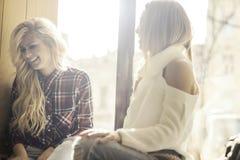 Två flickor som har gyckel, medan dricka kaffe Arkivbilder