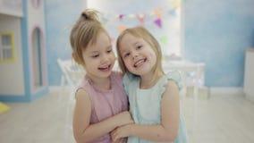 Två flickor som har gyckel och kramar sig som framme står av kameran stock video