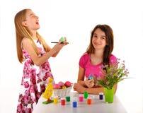 Två flickor som har roliga målningpåskägg arkivbilder