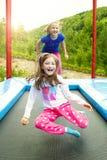 Två flickor som hoppar på trampolinen Fotografering för Bildbyråer
